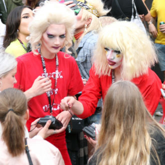 Performers in red drag outfits talk with fans.