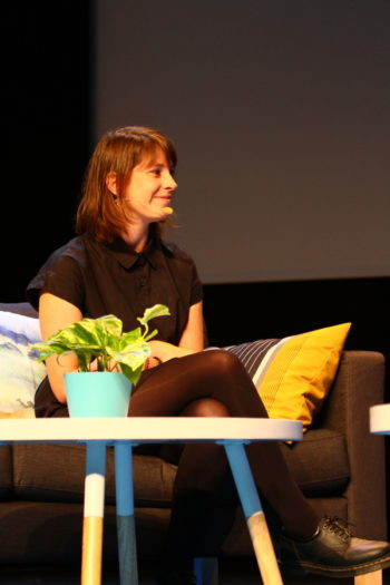 A woman, technology journalist Molly Schwartz, sits on a couch at a panel discussion.