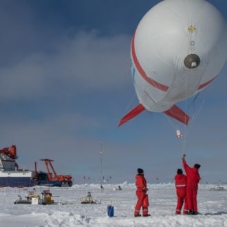 Three people in a snowy landscape getting ready to release a weather balloon, a ship in the background.