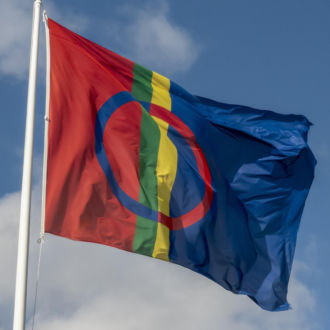 The Sámi flag flying in a flagpole against a blue sky.