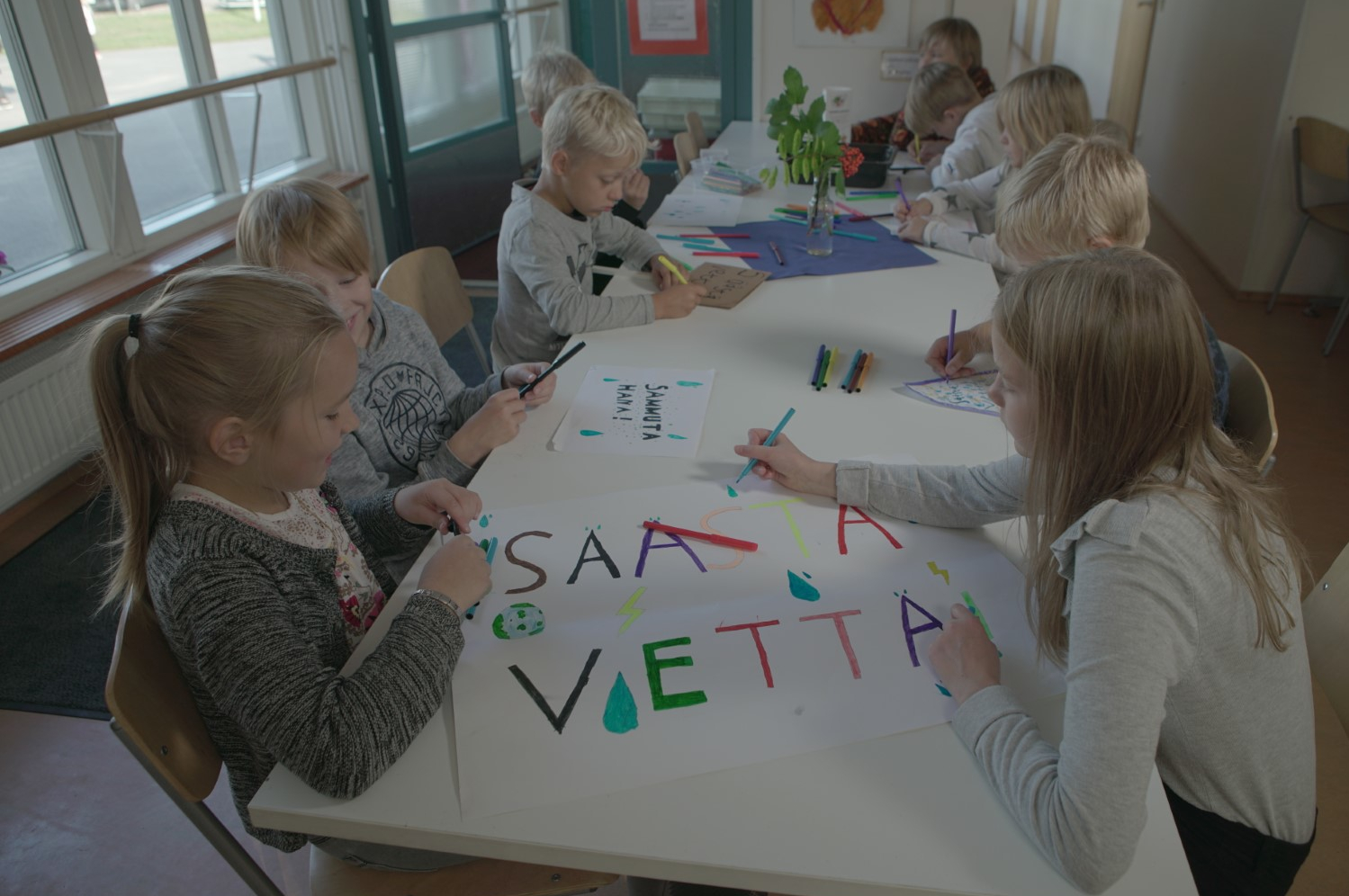 Schoolchildren sit around a long table drawing.