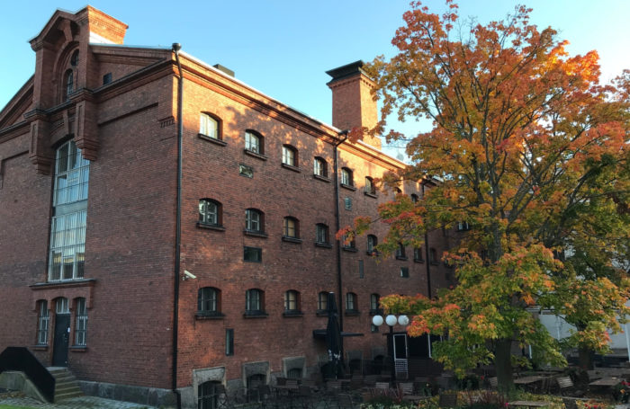Maple trees stand in front of a red brick building.