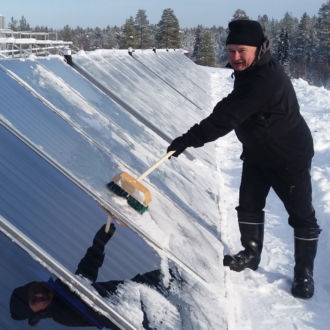A man uses a broom to clear snow from solar panels.