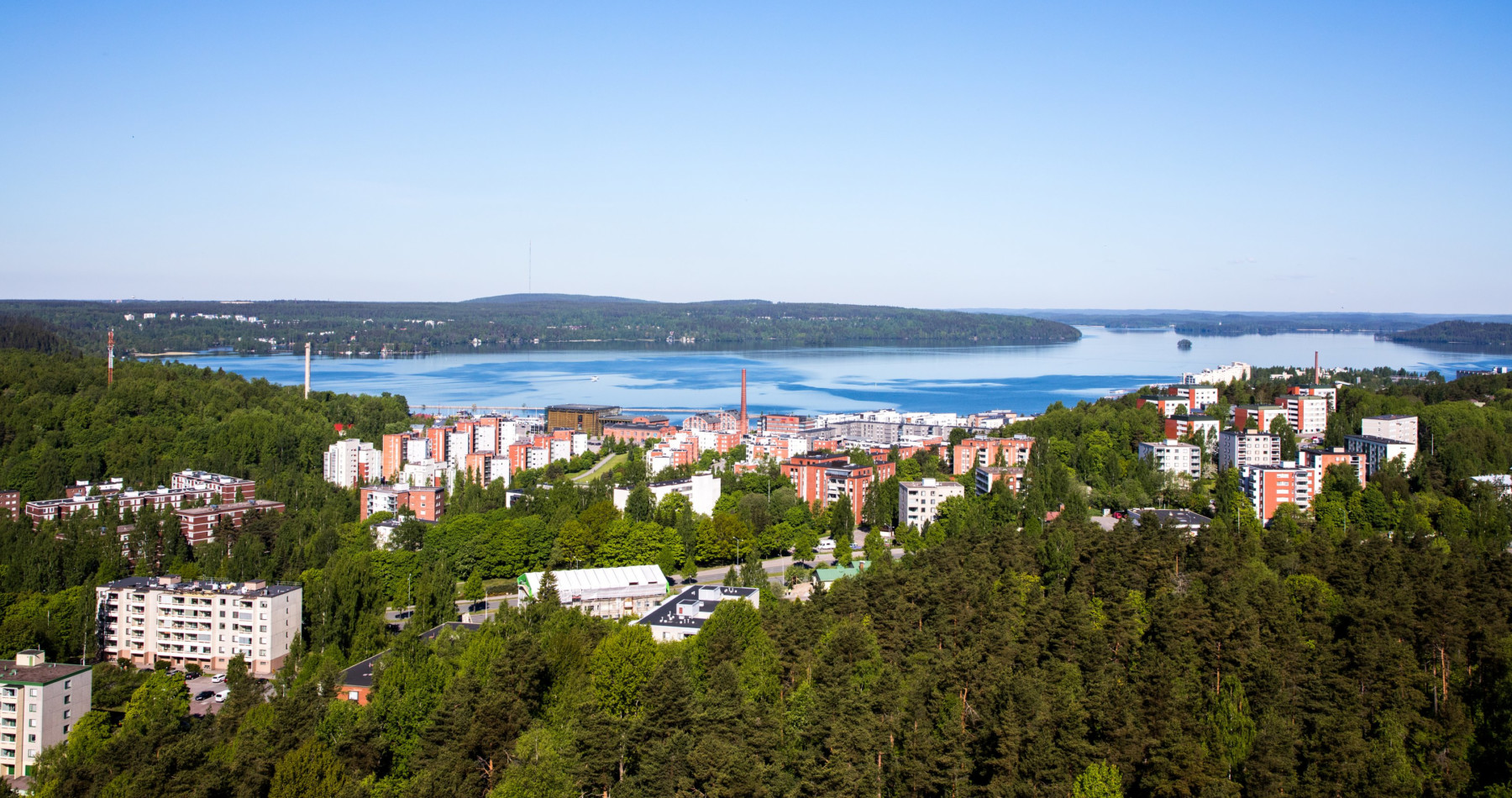 A panoramic view of a city beside a lake.
