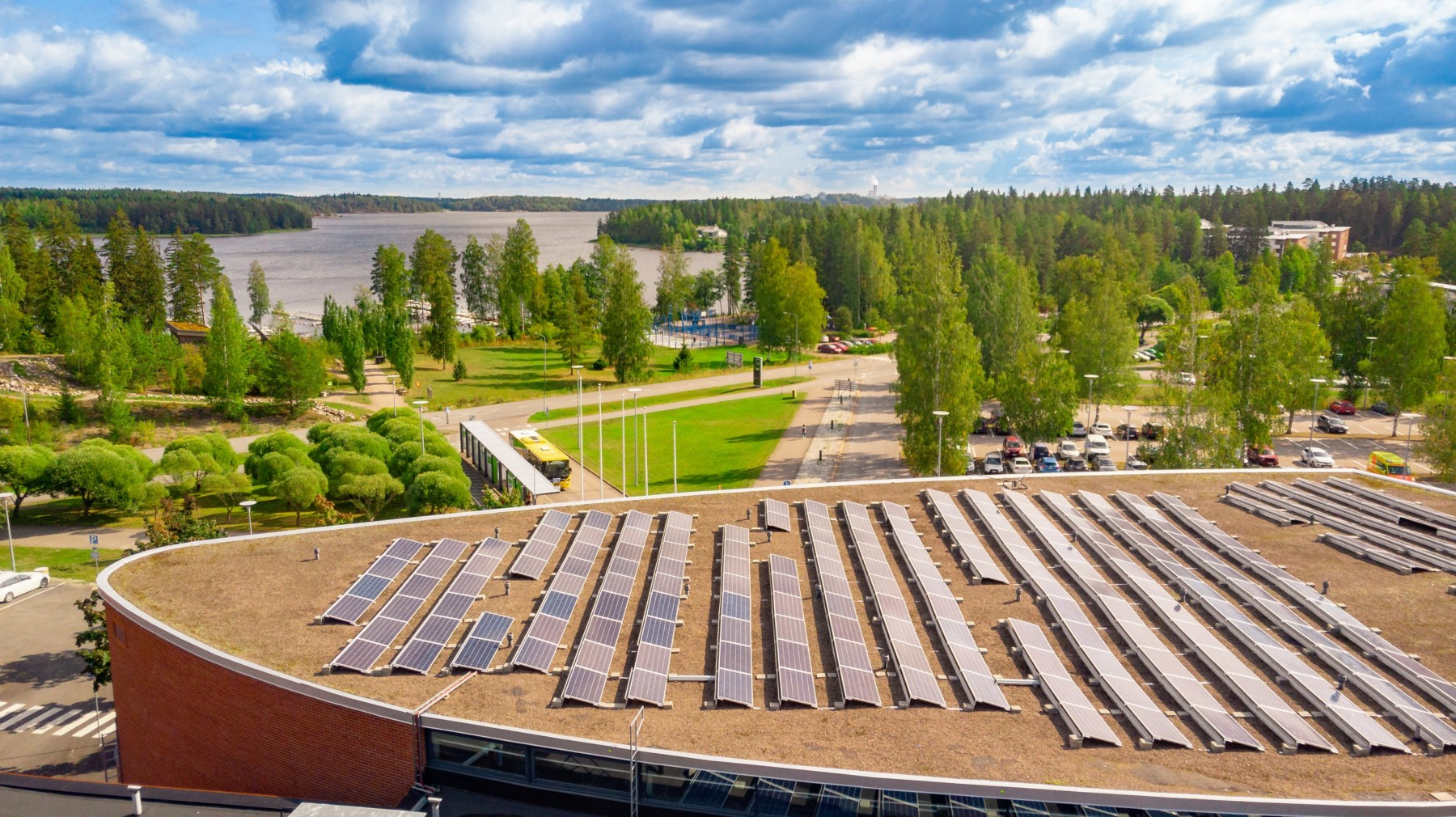 Solar panels line the roof a university building, with trees and a lake in the background.