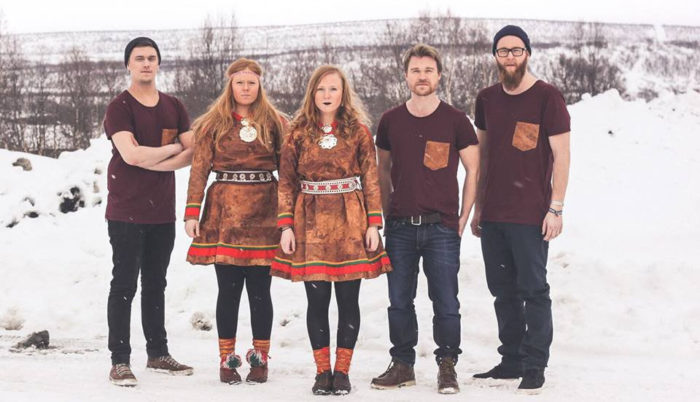 Three men and two women standing outside in the snow. The men are wearing t-shirts and the women are dressed in traditional Sámi dresses.