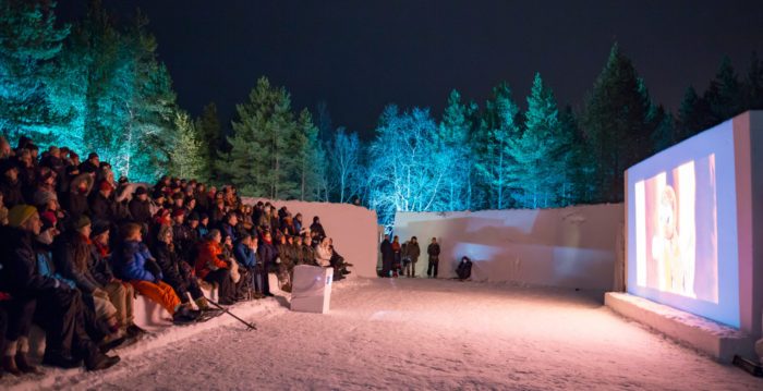 A crowd of people sitting outside on seats made of snow watching a film from a big screen.