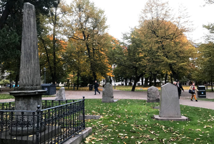 Tombstones and burial monuments stand in a park where autumn leaves have fallen from the trees.