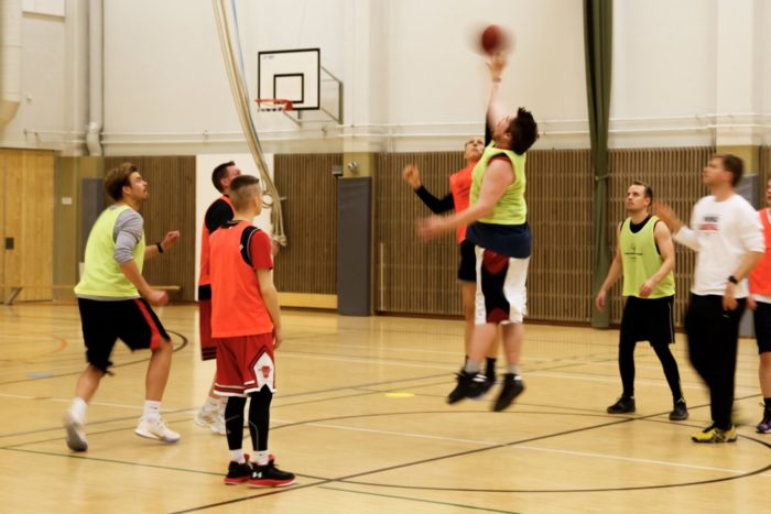 Two basketball players jump to reach the ball while other players wait around them.