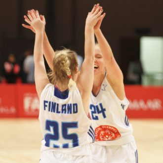 Two basketball players in Finnish national team jerseys give each other a high-five.