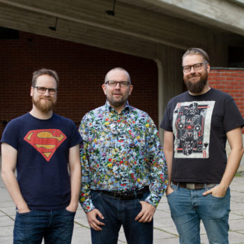 The founders of Superlect stand with their hands in their pockets in front of a red brick building.