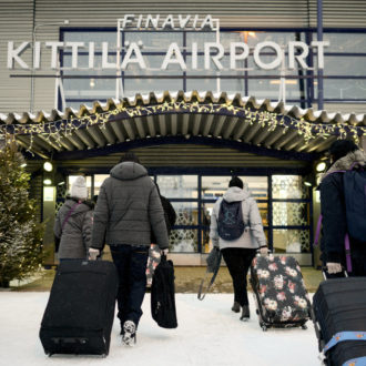 People pulling their suitcases towards a building with a sign that says Kittilä Airport.