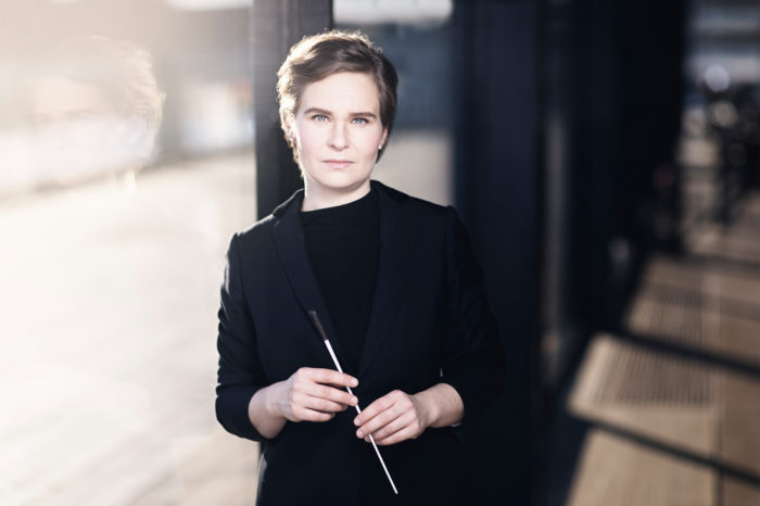 Portrait of conductor Eva Ollikainen, dressed in all black, holding a conductor's baton.
