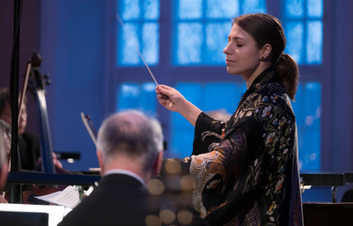 Conductor Dalia Stasevska leading an orchestra with her eyes closed.