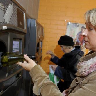 Une femme introduit une bouteille dans une machine à consigne.