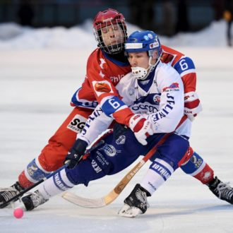 Two men playing bandy.