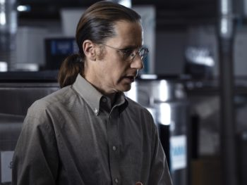 A man wearing wire-rim glasses and a grey shirt with the top button undone looks to his left in a scientific lab, showing his profile and his long hair in a ponytail.