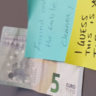 Close-up of a five-euro bill and post-it notes on a table.