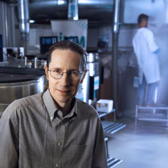 A man wearing wire-rim glasses and a grey shirt with the top button undone poses for a portrait in a scientific lab.