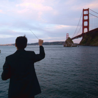 A man, his back to the camera, waves a conductor's baton on the shore by the Golden Gate bridge.