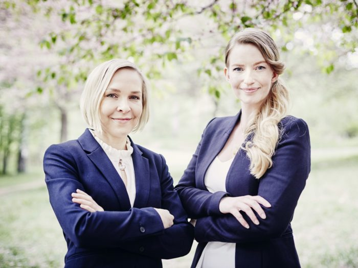 Two women in smart business attire stand with their arms crossed. In the background is a park with blossoming cherry trees.