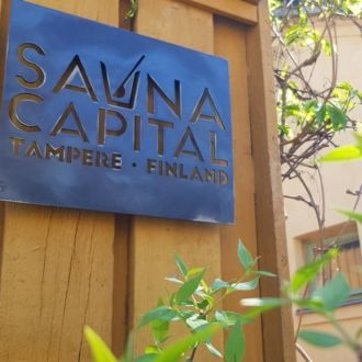 A blue sign on a yellow wooden wall reads, Sauna Capital, Tampere, Finland.