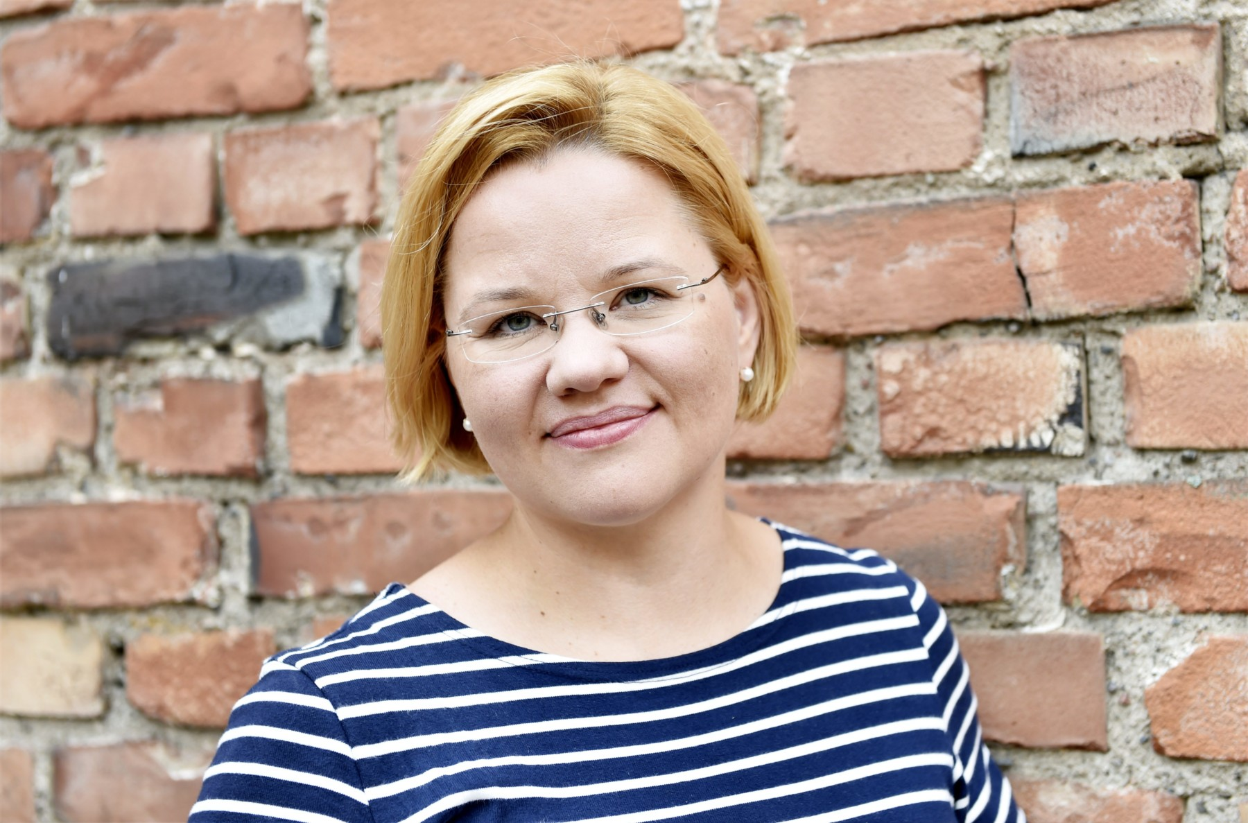 Portrait of professor Minna Palmroth in front of a red brick wall.