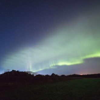 Green aurora borealis on a night sky over a field.