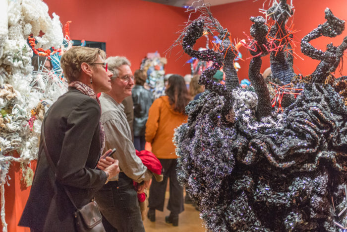 Two elderly people marvelling at an installation of crocheted sculptures that resemble coral reefs.