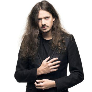 Мужчина в черной рубашке и черной куртке смотрит в камеру с одной рукой на груди и второй на животе.