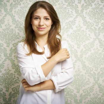 In front of a floral wallpaper pattern, a woman in a white shirt looks into the camera.