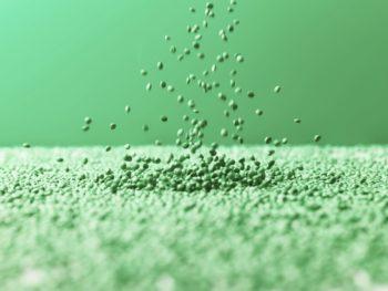 De petits pellets verts de forme circulaire tombent au milieu d'une surface complètement recouverte de pellets du même type semblant former une mer.