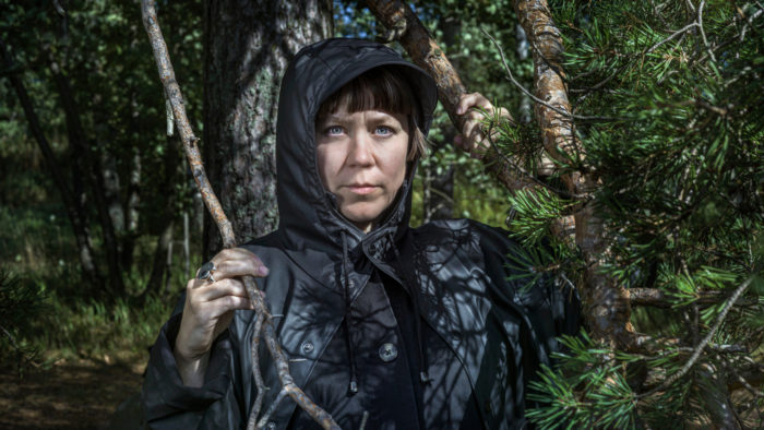 Portrait of a woman, artist Hanna Tuulikki, standing in a forest wearing a black hooded jacket.