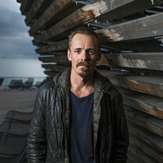 A portrait of Finnish actor Jasper Pääkkönen standing outside next to a wooden wall