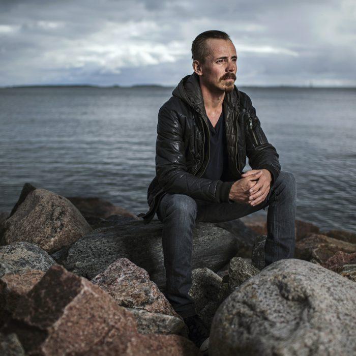 Ator finlandês Jasper Pääkkönen sentado em uma pedra em frente ao mar Báltico.