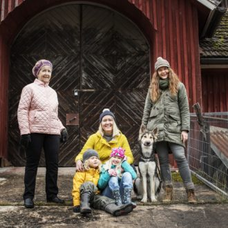 Wearing jackets and hats that suggest cool weather, an older woman, two women in their thirties and two young children pose together with a large dog in front of a wooden building.
