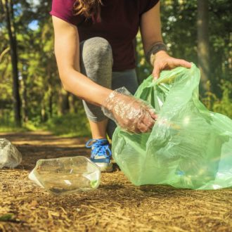In a forest, a person is putting pieces of plastic trash in a bag.