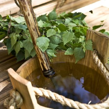 Un fagot de petites branches feuillues est posé à côté d'un baquet en bois où est immergée une louche.