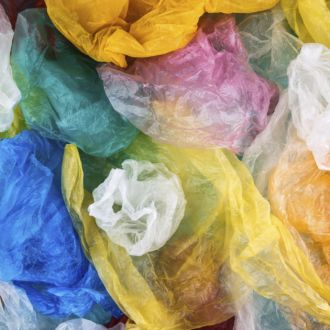 Plastic bags of various colours are jumbled together.