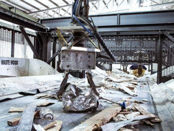 An enormous mechanical claw is picking up a hunk of metal from a conveyor belt carrying scraps of used wood and metal through a factory setting.