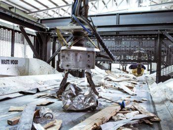 Uma enorme garra mecânica pega um pedaço de metal de uma correia transportadora que carrega restos de madeira e metal usados através de uma configuração de fábrica.