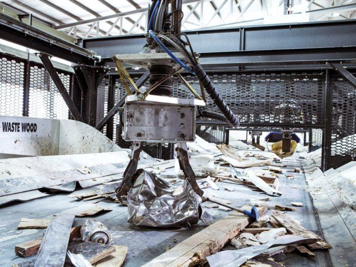 Гигантские механические клещи поднимают большой кусок металла с конвейерной ленты, по которой на заводе двигают использованное дерево и металл.
