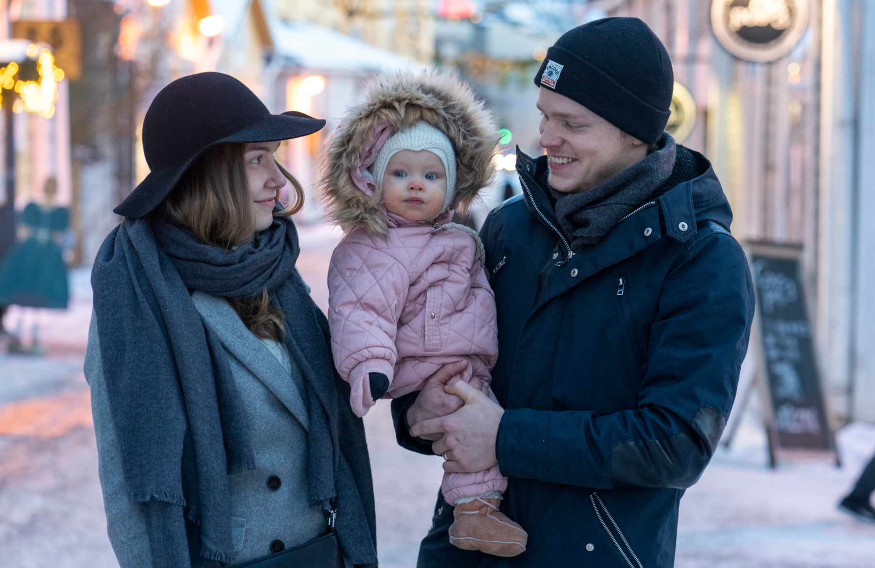 A happy family of three standing outside on the street in wintertime