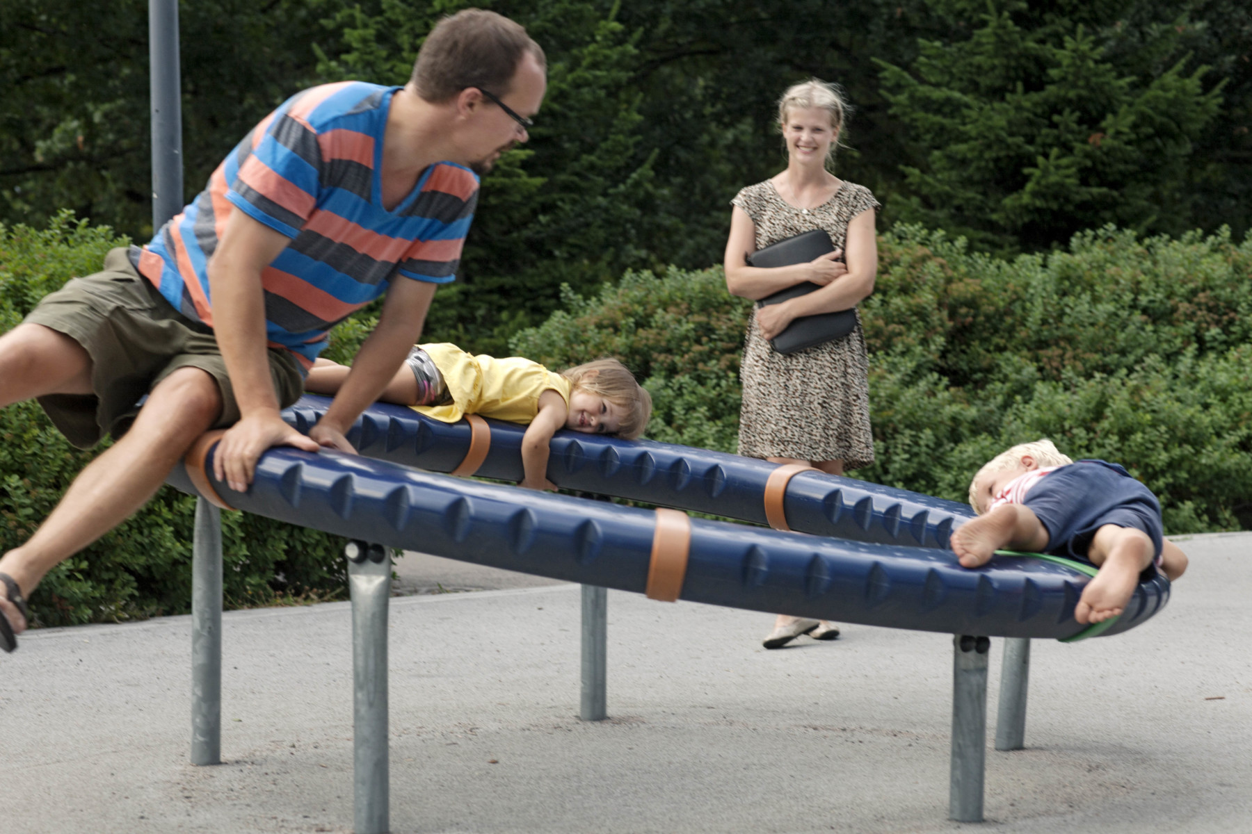 A family of four at the playground. The father plays with the two children