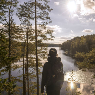 A hiker takes in a sunlit view of lake and forest in Repovesi National Park, southern Finland.