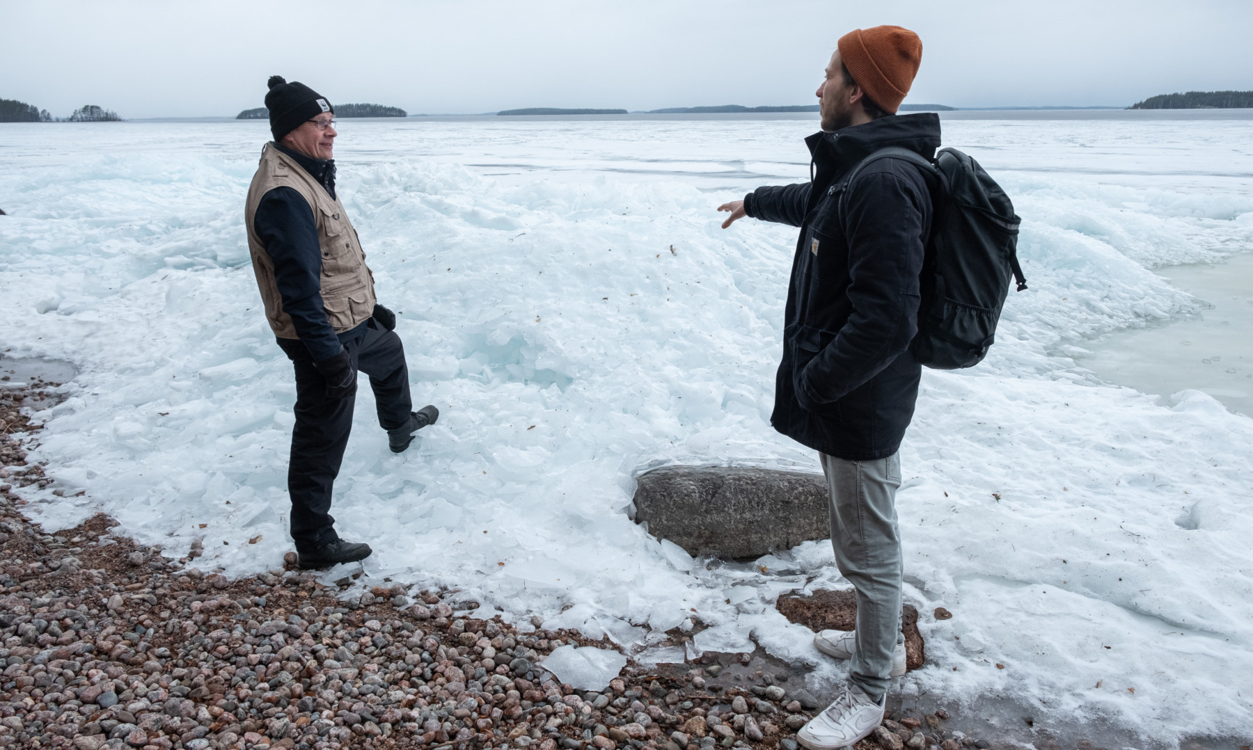 Two men survey piles of ice on a lakeshore.