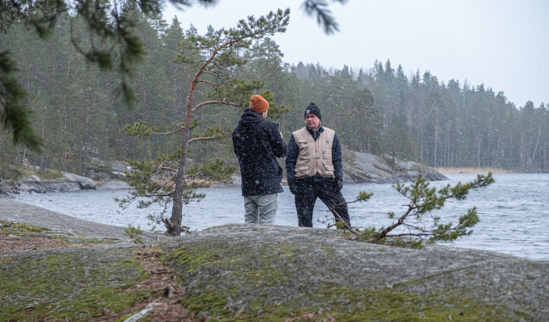 Two men stand beside a lake.