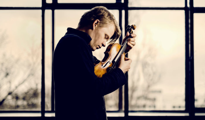 Violinist Pekka Kuusisto strums his violin without a bow in front of a window.