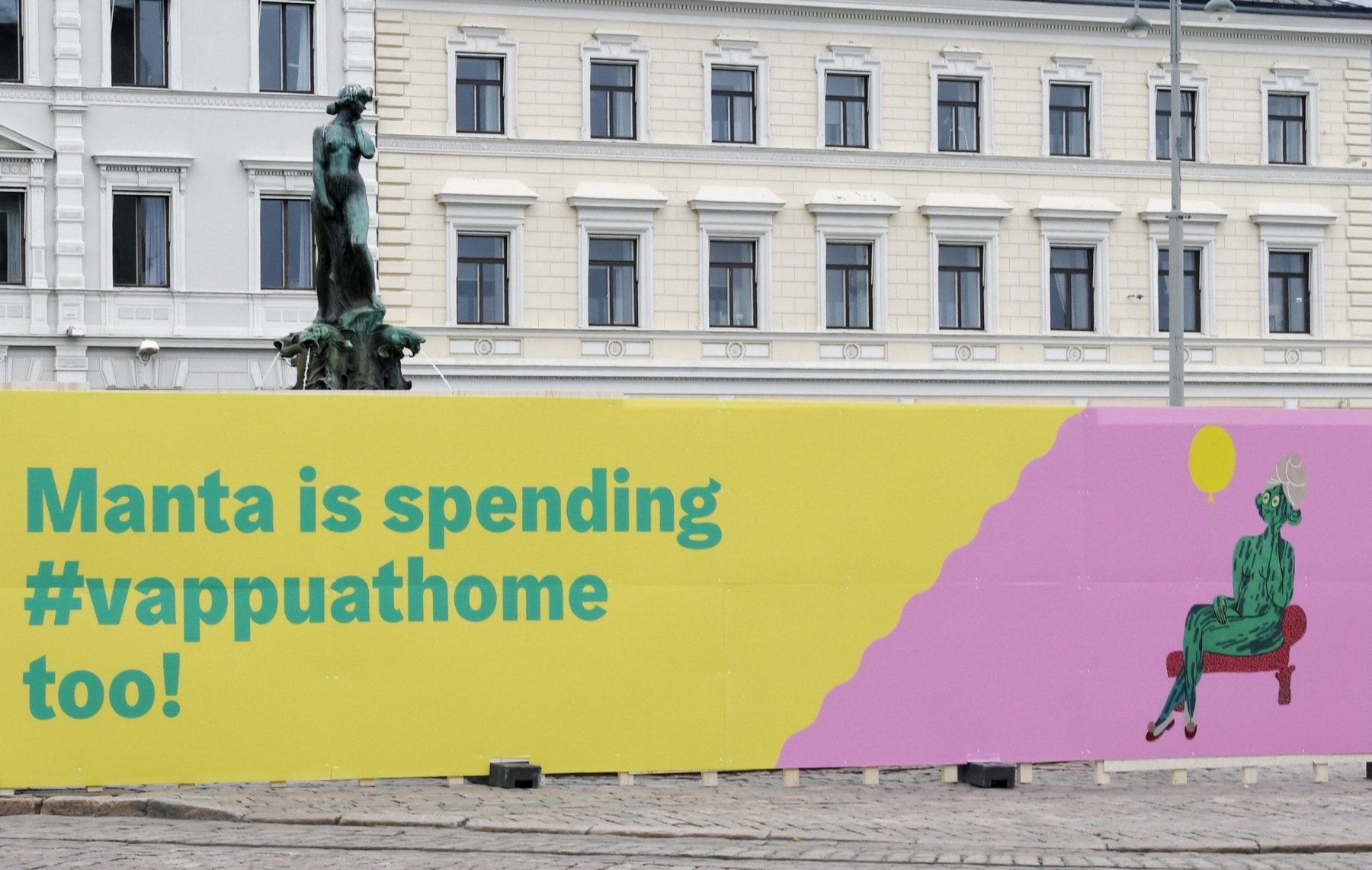 On Helsinki's Market Square, the Havis Amanda statue is surrounding by a temporary wall. A sign says that she is spending May Day at home.
