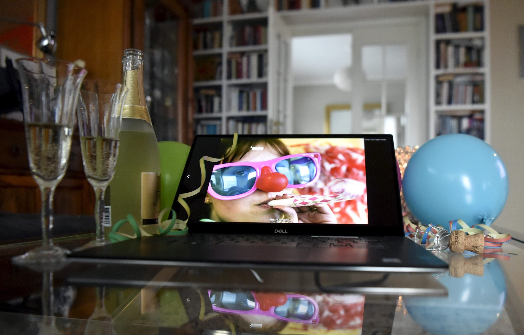 In a home, an open laptop computer screen shows a fun event. Beside it on the table are a balloon, a bottle of champagne and two glasses.
